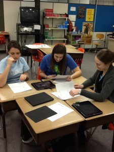Teacher and two students using iPad